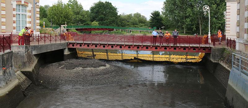 Torkar upp tillförselkanalen i den gamla hydrauliska anläggningen i Le Mans. Huisnesfloden. Vy över det tömda området nedströms om skärmen.