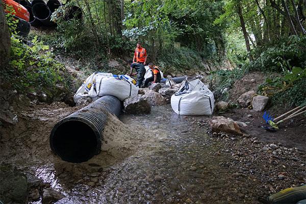 Kilning av ett ECOPAL-rör med lera, uppströms sida. Avsluta som kommer att ta emot den främre kanten av Water-Gate © flexibla kofferdamm
