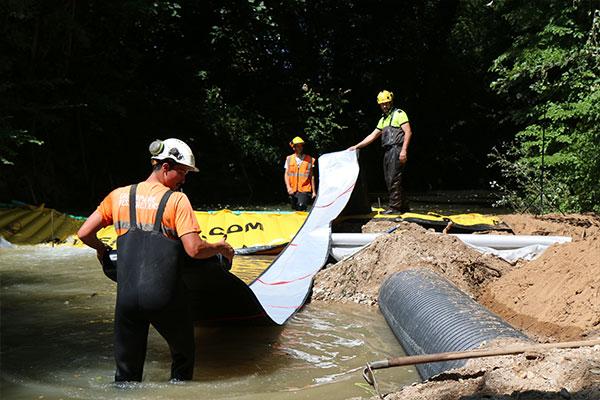 Den flexibla utloppsslangen DP-3075, 450 mm i diameter, är fäst vid Water-Gate ©-dammen. Sedan rullar vi ut helt nedströms innan vi fyller vattnet.