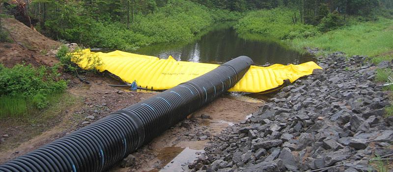 Flexibel Water-Gate © kofferdamm för arbete i floder. Avtagbar damm med bypass vid rörledning.